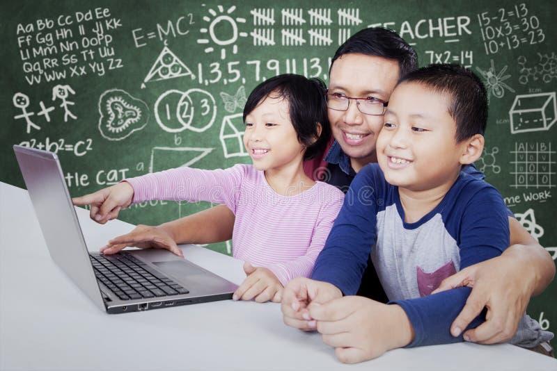 Professor elementar que usa o portátil com estudantes fotografia de stock