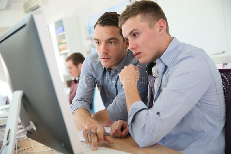 Professor en student die aan computer werken royalty-vrije stock foto's