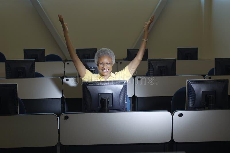 Professor fêmea Celebrating Victory In Computer Classroom imagem de stock royalty free