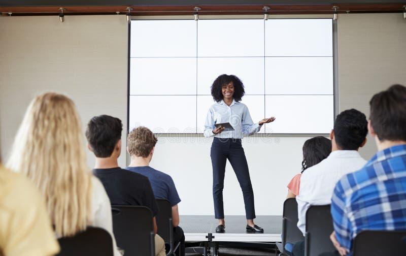 Professor fêmea With Digital Tablet que dá a apresentação à turma da escola secundária em Front Of Screen fotografia de stock royalty free