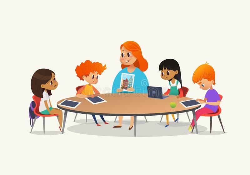Professor fêmea do ruivo que mostra a imagem às crianças que sentam-se em torno da mesa redonda na classe com o PC do portátil e  ilustração do vetor