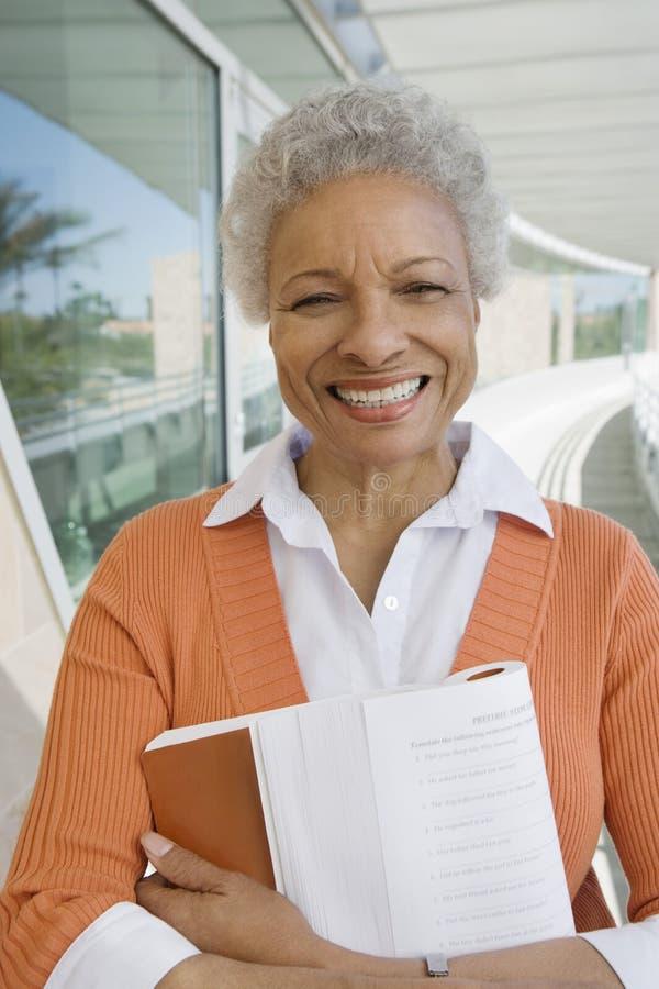 Professor fêmea feliz With Book fotografia de stock