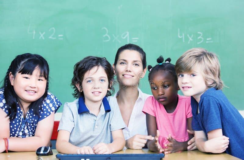 Professor fêmea feliz com sua sala de aula do multirace na mesa da escola imagem de stock royalty free