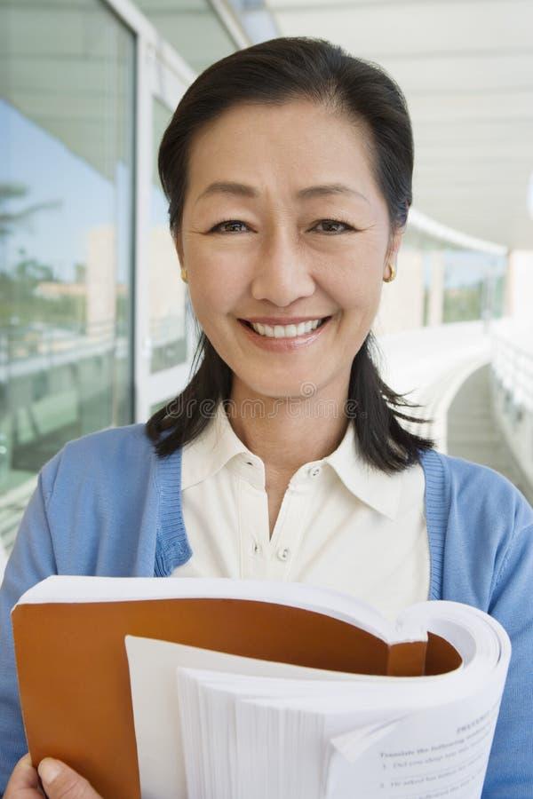 Professor fêmea Holding Book imagens de stock