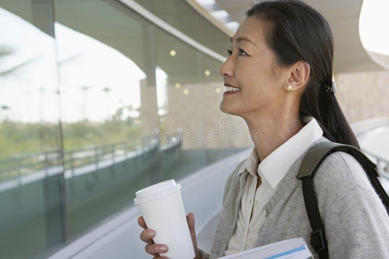 Professor fêmea Holding Disposable Cup imagem de stock royalty free