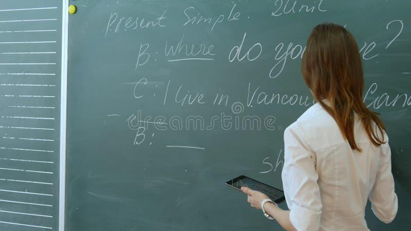Professor fêmea novo na sala de aula da escola que fala à classe na lição inglesa imagens de stock