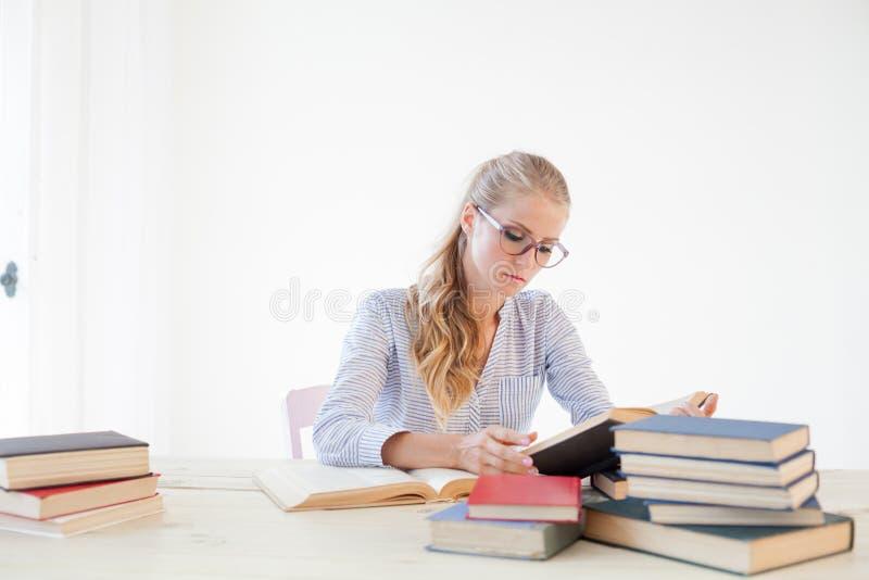 Professor fêmea que senta-se em uma tabela do escritório de muitos livros foto de stock royalty free