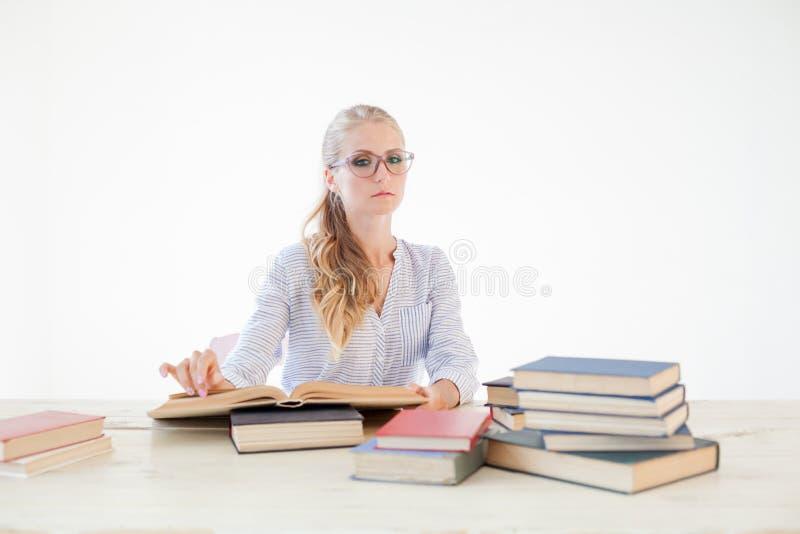 Professor fêmea que senta-se em uma tabela do escritório de muitos livros imagem de stock