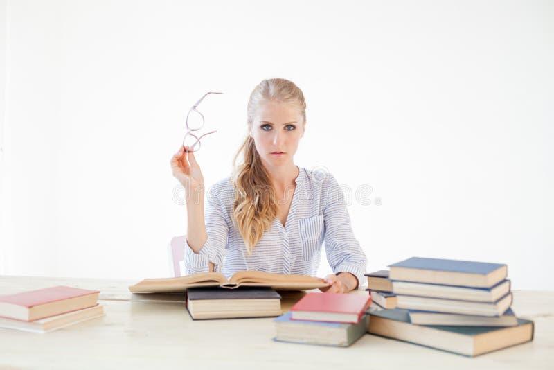Professor fêmea que senta-se em uma tabela do escritório de muitos livros imagens de stock