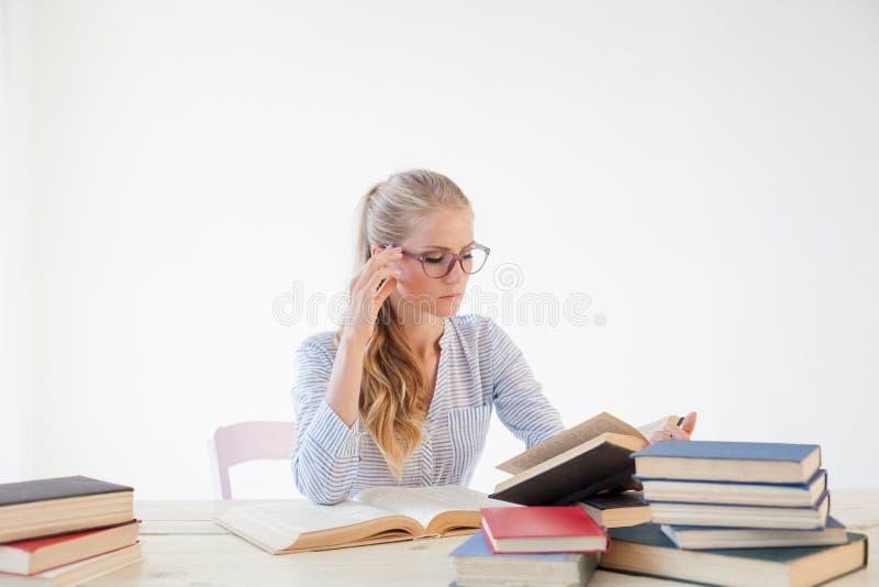 Professor fêmea que senta-se em uma tabela do escritório de muitos livros fotos de stock
