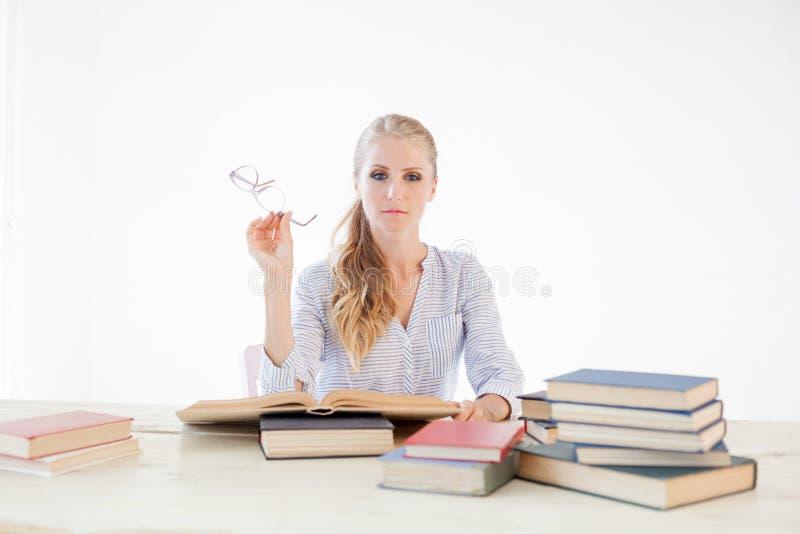 Professor fêmea que senta-se em uma tabela do escritório de muitos livros fotos de stock royalty free