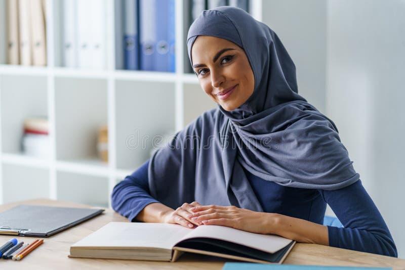 Professor fêmea que senta-se na mesa foto de stock