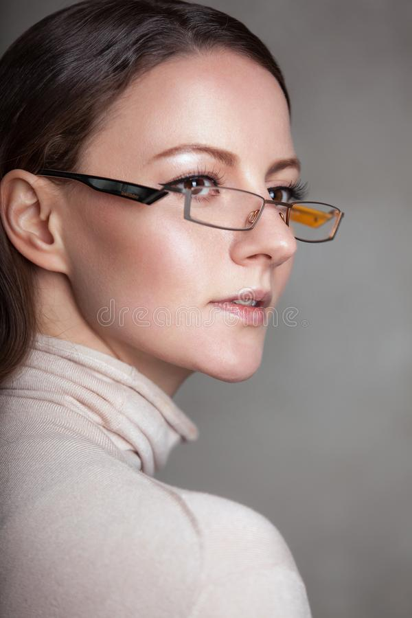 Professor fêmea Wearing Glasses da mulher no pescoço bege da tartaruga da camiseta da luz branca fotografia de stock royalty free