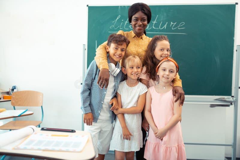 Professor feliz de amor que abraça seus alunos diligentes espertos fotos de stock royalty free