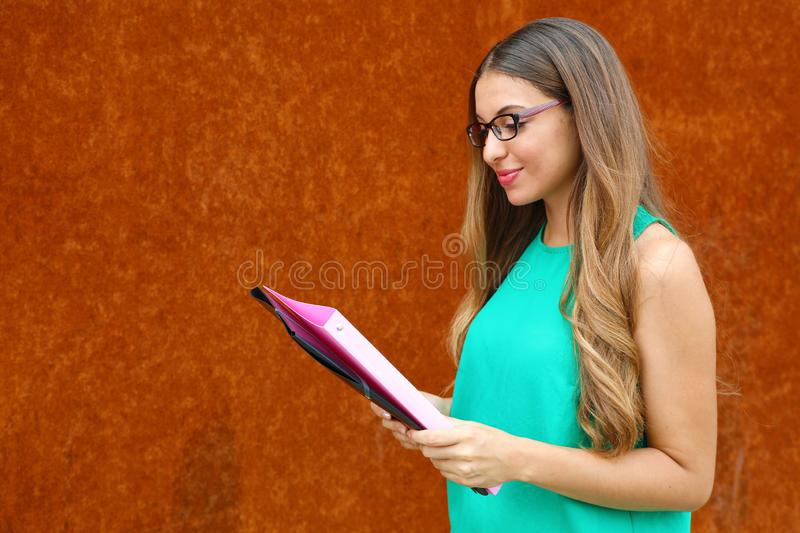 Professor female or business woman reading documents outdoor with copy space on rust background stock photography