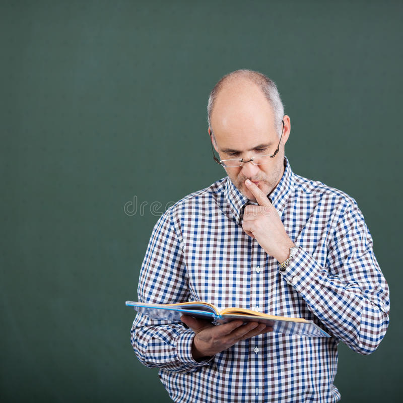 Professor With Finger On Lips Standing Against Chalkboard stock images