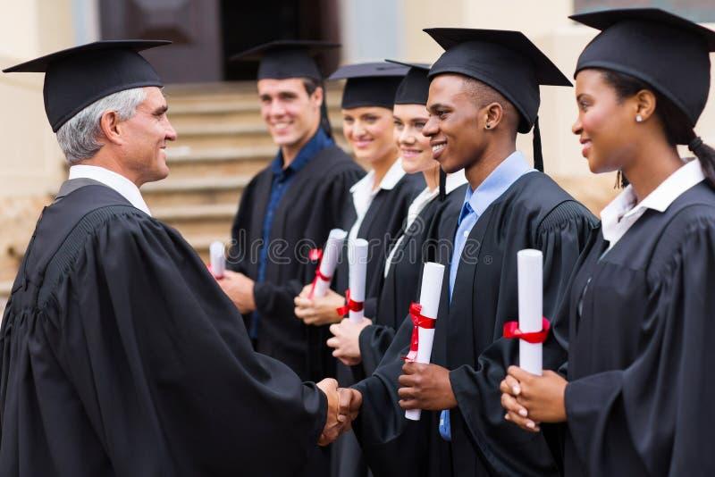 Professor handshaking graduates. Senior university professor handshaking with young graduates stock image