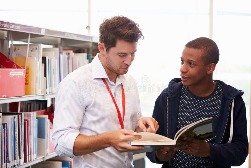 Professor Helping College Student com estudos na biblioteca foto de stock royalty free