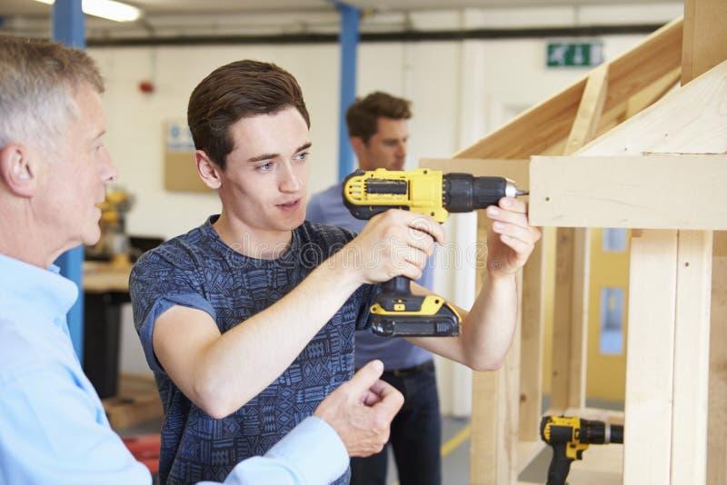 Professor Helping College Student que estuda a carpintaria fotos de stock royalty free