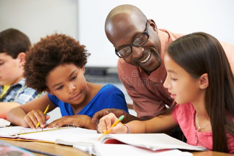 Professor Helping Pupils Studying em mesas na sala de aula imagens de stock royalty free