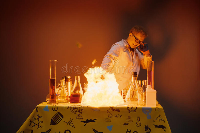 Professor in the laboratory, conducting chemical experiments with explosions royalty free stock photo