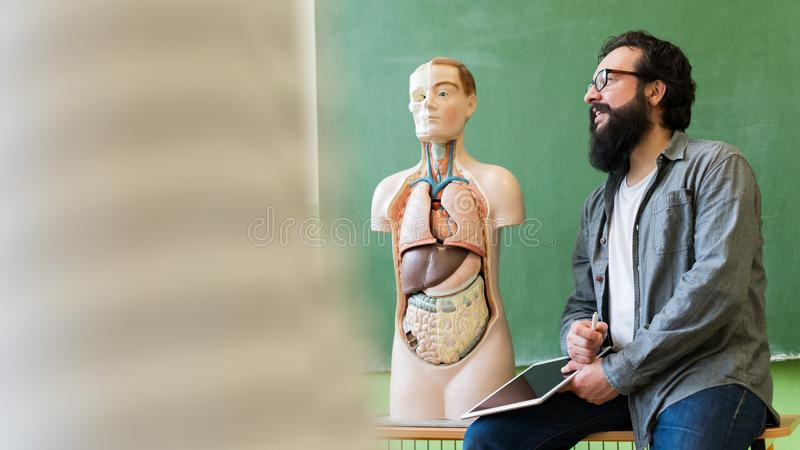 Professor latino-americano masculino novo na turma de Biologia, guardando a tabuleta digital e ensinando a anatomia do corpo huma fotos de stock