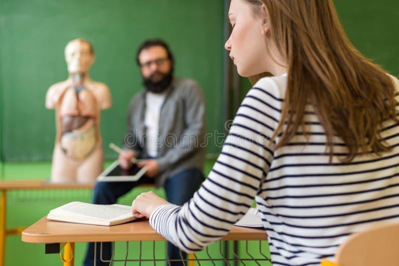 Professor latino-americano masculino novo na turma de Biologia, guardando a tabuleta digital e ensinando a anatomia do corpo huma imagens de stock