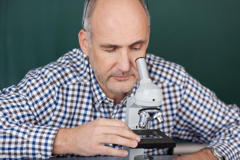 Professor Looking Through Microscope in Wetenschapsklasse stock afbeeldingen