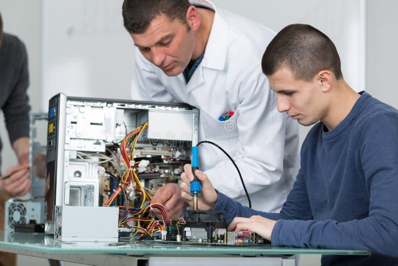 Professor masculino que ajuda ao homem novo no computador da fixação foto de stock