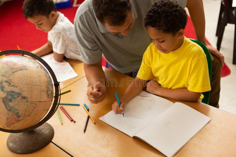 Professor masculino que ensina uma estudante em uma sala de aula fotos de stock royalty free