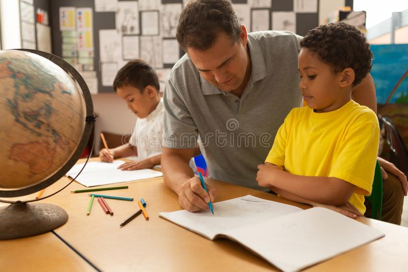 Professor masculino que ensina uma estudante em uma sala de aula imagem de stock royalty free