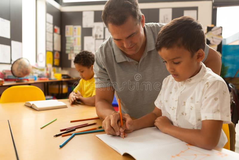 Professor masculino que ensina uma estudante em uma sala de aula imagem de stock