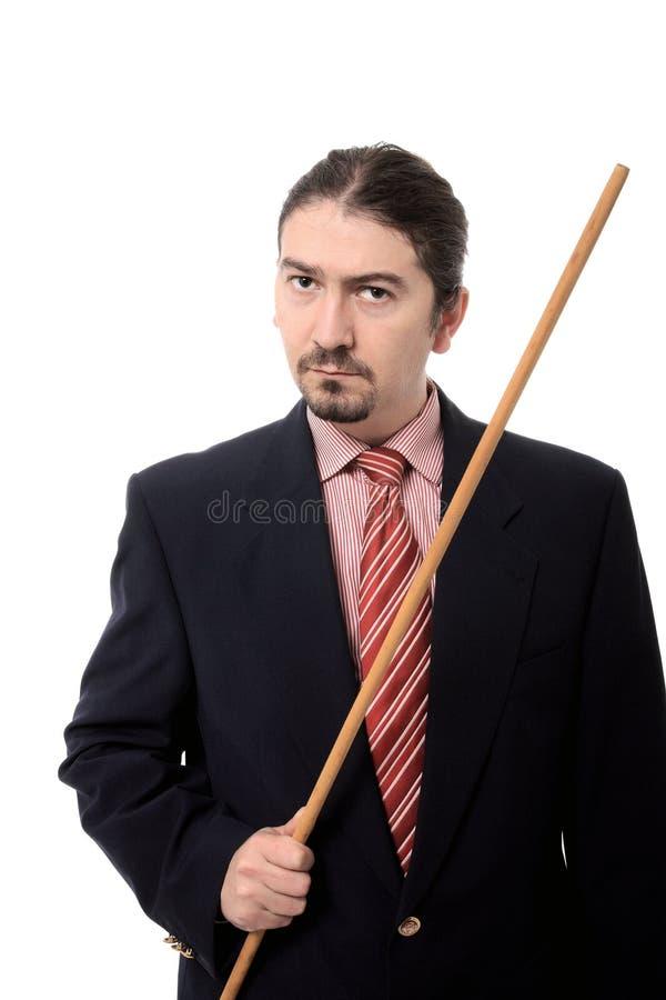 Professor masculino que prende uma vara de madeira longa imagens de stock