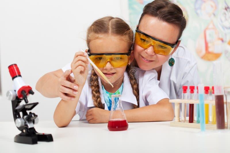 Professor novo com o estudante pequeno na classe elementar da ciência imagens de stock