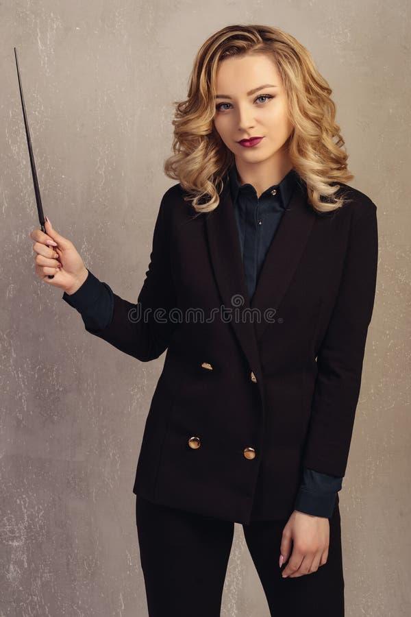Professor novo da mulher de negócio com ponteiro à disposição perto de uma parede textured cinzenta foto de stock