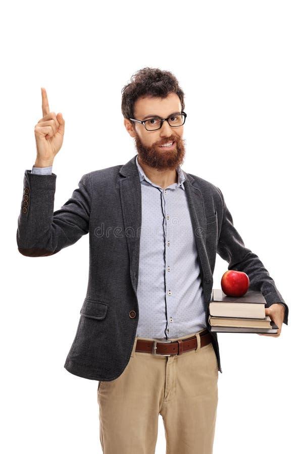 Professor novo que tem uma ideia e que aponta acima foto de stock royalty free