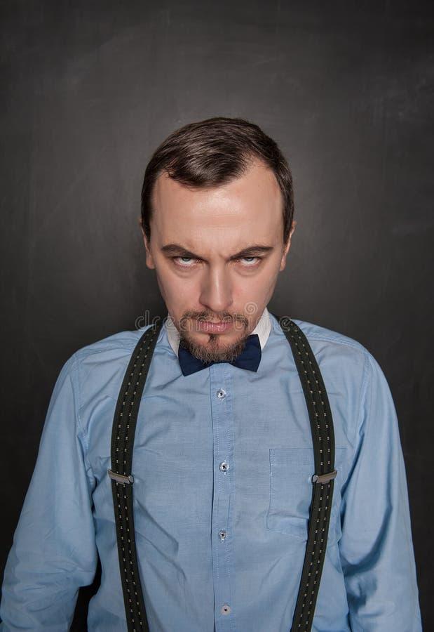 Professor ou homem de negócio sério que olha o no quadro-negro fotografia de stock