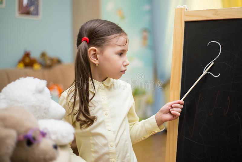Professor pequeno A moça bonita está ensinando brinquedos em casa sobre foto de stock