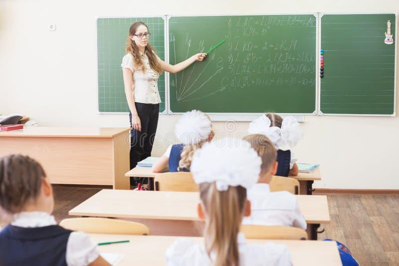 Professor perto das crianças de ensino do quadro-negro matemática ou geometria, guardando o ponteiro imagens de stock
