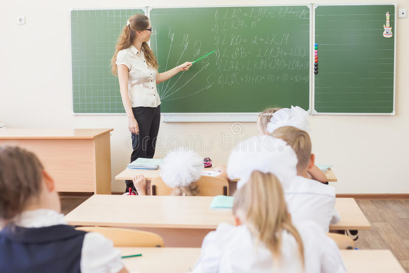 Professor perto das crianças de ensino do quadro-negro matemática ou geometria, guardando o ponteiro imagem de stock