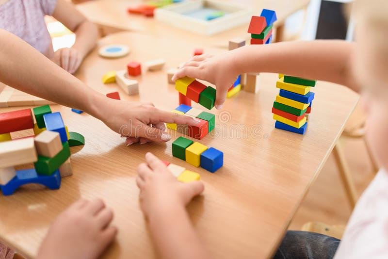 Professor pré-escolar com as crianças que jogam com os brinquedos didáticos de madeira coloridos no jardim de infância fotos de stock royalty free