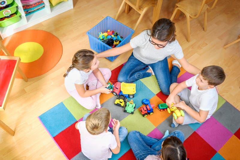 Professor pré-escolar que fala ao grupo de crianças que sentam-se em um assoalho no jardim de infância imagens de stock