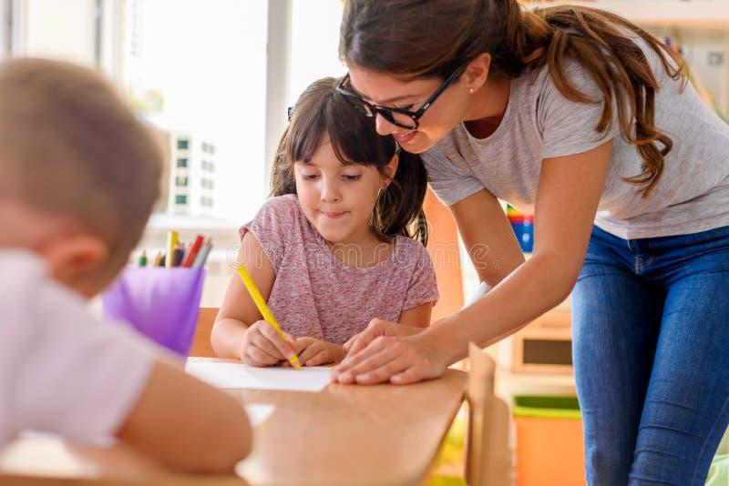 Professor pré-escolar que olha a criança esperta no jardim de infância fotos de stock royalty free