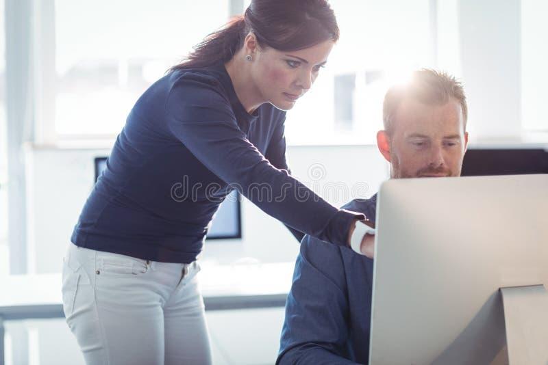 Professor que ajuda ao estudante maduro na sala de computador imagem de stock royalty free