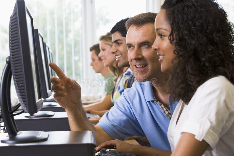Professor que ajuda ao estudante universitário em computadores imagem de stock