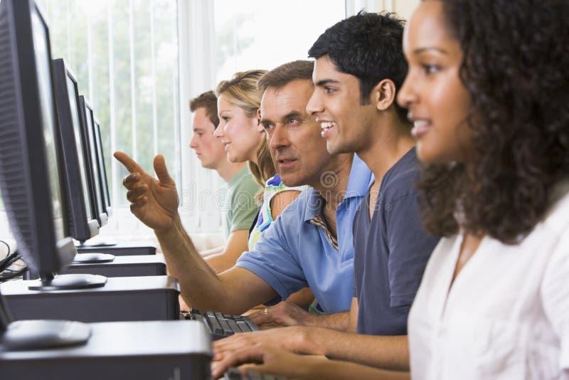 Professor que ajuda ao estudante universitário em computadores imagens de stock royalty free