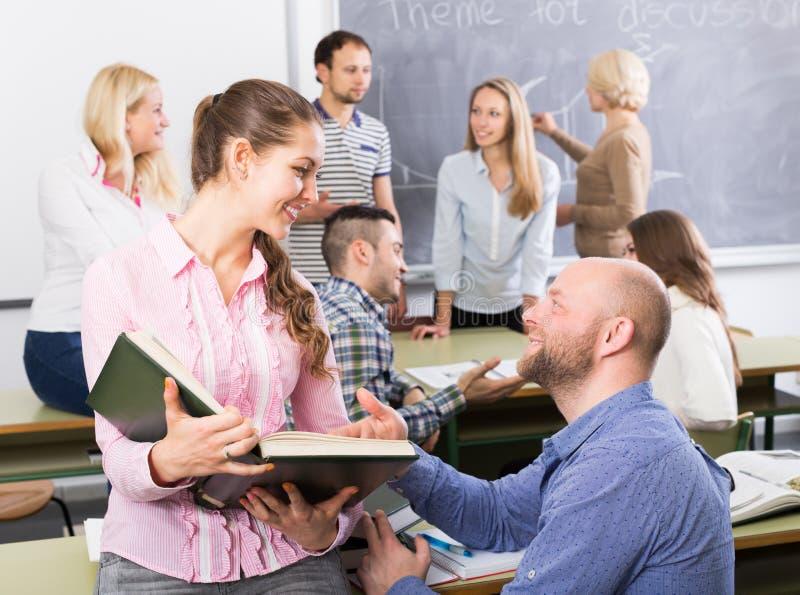 Professor que consulta estudantes diferentes da idade foto de stock