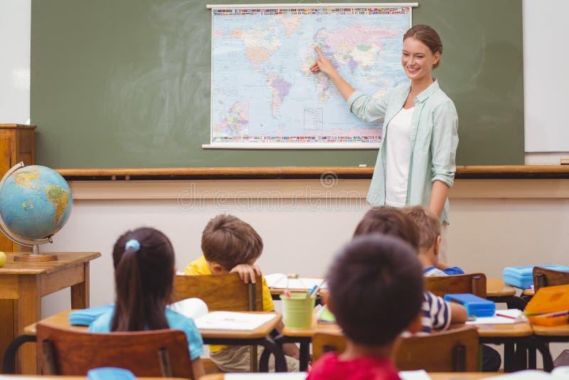 Professor que dá uma lição da geografia na sala de aula imagens de stock