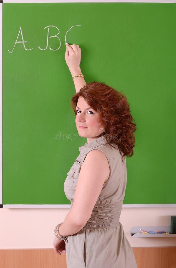 Professor que escreve o ABC em uma placa na escola fotos de stock