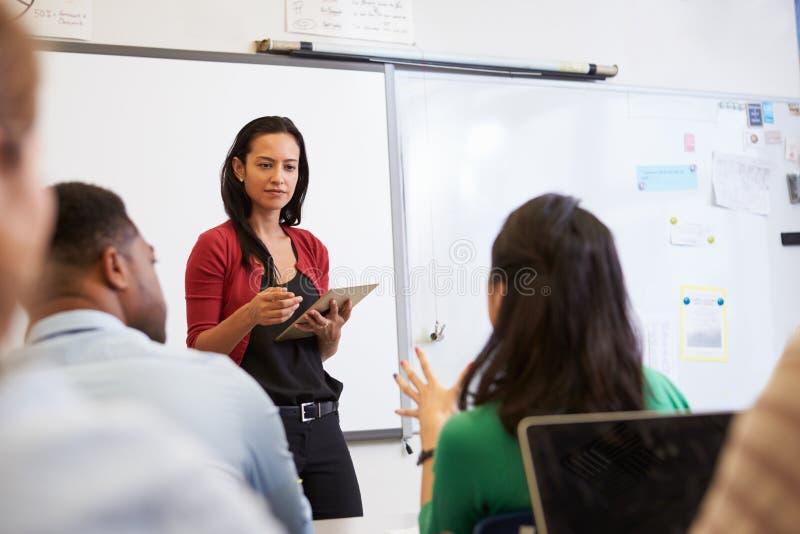 Professor que escuta estudantes em uma classe do ensino para adultos imagem de stock royalty free